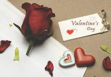 Rose de rouge sous enveloppe sur un fond brun clair Photographie stock