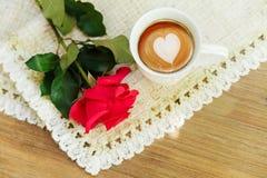 Rose de rouge sur la serviette de table rugueuse avec la tasse de coffe Tabl en bois Photo stock