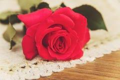 Rose de rouge sur la serviette de table rugueuse Fond en bois de Tableau selec Photos stock