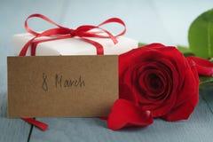 Rose de rouge sur la table en bois bleue avec la carte de papier de cadeau et du 8 mars Images stock