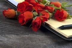 Rose de rouge sur un carnet et un crayon Images libres de droits