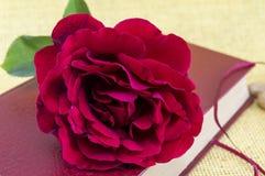 Rose de rouge sur un livre fermé Photographie stock libre de droits