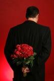 Rose della holding dell'uomo dietro suo indietro Immagini Stock