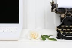 Rose on Desk Between Laptop and Typewriter Royalty Free Stock Image