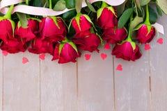 Rose di fioritura di rosso su legno Immagine Stock