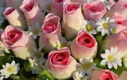 Rose di seta e fiori bianchi. Fotografia Stock