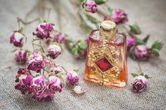Rose di tè asciutte e bottiglia di profumo d'annata sulla tela di sacco fotografia stock libera da diritti
