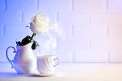 Rose douce de blanc dans un vase et une tasse de café Foyer sélectif Fond avec l'espace de copie Images stock