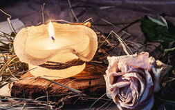 Rose, dry hay and a candle on a table stock photography