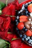 Rose e dolce di cioccolato rosso scuro con le bacche Immagini Stock