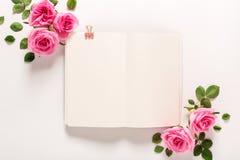 Rose e vista superiore del taccuino in bianco Fotografia Stock