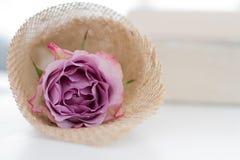 Rose in einem natürlichen Paket auf dem Tisch Stockfotografie
