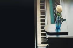 Rose en el florero en el piano de cola foto de archivo libre de regalías