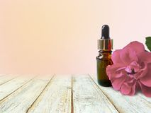Rose, essential oil bottle with empty table on yellow background. Mock up spa aromatherapy concept royalty free stock photos