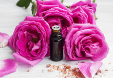 Rose essential oil in a bottle with rose flowers Royalty Free Stock Photo