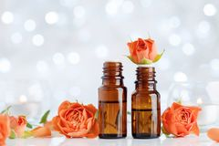 Rose essential oil bottles on white table with bokeh effect. Spa, aromatherapy, wellness, beauty background. royalty free stock photo
