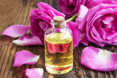 Rose essential oil with pink roses and petals on wooden board Stock Photo