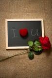 Rose et anneau de rouge dans la boîte se trouvant sur le tableau Photo stock