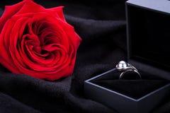Rose et bague à diamant de rouge dans une boîte Photo stock
