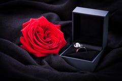 Rose et bague à diamant de rouge dans une boîte Images stock