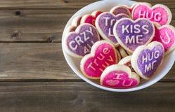 Rose et biscuits en forme de coeur pourpres sur le fond en bois Photographie stock