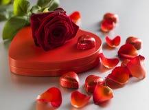 Rose et boîte de rouge avec les coeurs rouges sur un fond blanc Image stock