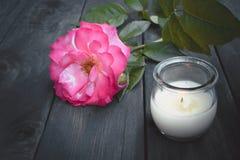 Rose et bougie brûlante sur un vieux conseil en bois Fleurissez la trame photo libre de droits
