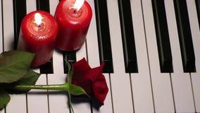 Rose et bougie sur des clés de piano