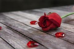 Rose et coeurs rouges sur le plancher en bois Photo stock