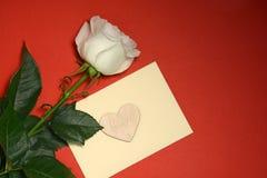 Rose et enveloppe de blanc avec le coeur sur le fond rouge Images stock