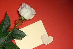Rose et enveloppe de blanc avec le coeur sur le fond rouge Photo libre de droits