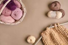 Rose et laine de tricotage brune et tricotage sur des aiguilles de tricotage sur le fond beige Vue supérieure Copiez l'espace Photos stock