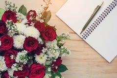 Rose et livre vide avec le stylo sur la table en bois Image libre de droits