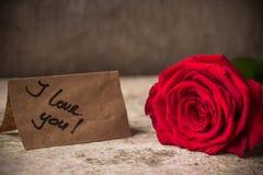 Rose et note de rouge je t'aime sur le papier de métier Images stock