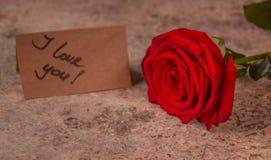 Rose et note de rouge je t'aime sur le papier de métier Images libres de droits