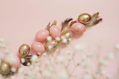 Rose et oeufs de pâques d'or Concept en pastel de Pâques avec des oeufs, des fleurs et des plumes Pastels ivres Image libre de droits