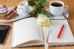 Rose et page vide de carnet sur le fond en bois Photo stock