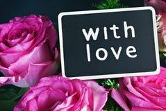 Rose et un tableau noir avec un souhait de l'amour Photographie stock