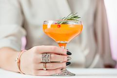 The rose exotic cocktails and fruits and female hand. The female hand and rose exotic cocktail and fruits on table Royalty Free Stock Image