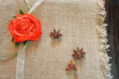 Rose from fabric and an anisetree lie on burlap. Horizontal format. Indoors. Without people. Top view. Color. Photo Royalty Free Stock Photos