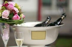Rose fleurit la bouteille refroidie à la glace de vin mousseux et de champagne dans l'espace des textes de copyspace de seau Photos stock