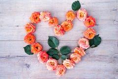 Rose fleurit le cadre de forme de coeur sur le fond en bois Configuration plate, vue supérieure Fond du `s de Valentine Photo libre de droits