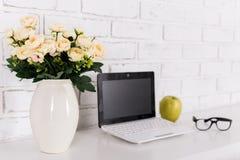 Rose fleurit sur le lieu de travail avec l'ordinateur portable moderne à la maison Photos libres de droits