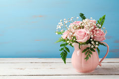 Rose flower bouquet in pink vase over wooden background Royalty Free Stock Photo