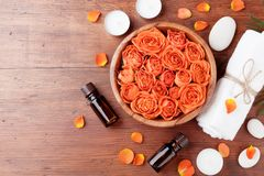 Rose flower in bowl, essential oil bottle, towel and candles on wooden table top view. Spa, aromatherapy, wellness, beauty. Royalty Free Stock Photos