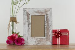 Rose flower, empty photo frame and gift boxes. On wooden table royalty free stock photography