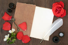 Rose Flower Essential Oil. Red rose flower and petals with hemp notebook, old quill feather pen and ink, with orange blossom and essential oil bottles on old oak Royalty Free Stock Photography