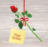 A rose flower is hanging on a red ribbon with a bow. Yellow shee. T of paper for notes. Sticker.Greeting card or invitation for a holiday. Empty place for text Stock Image