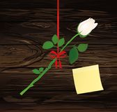 A rose flower is hanging on a red ribbon with a bow. Yellow shee. T of paper for notes. Sticker.Greeting card or invitation for a holiday. Empty place for text Royalty Free Stock Image