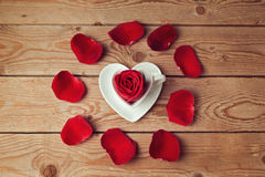 Rose flower petals and heart shape coffee cup on wooden table Royalty Free Stock Photos